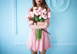 Beautiful young woman in pink dress holding spring pink flower bouquet on the blue background in the morning.