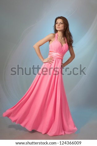 Beautiful young woman in pink evening dress, on grey background - stock photo