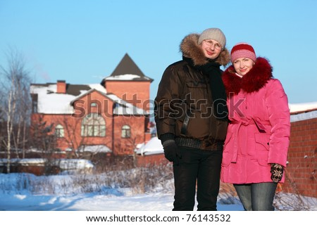 beautiful young woman in pink jacket and man in glasses standing outdoors at winter, house