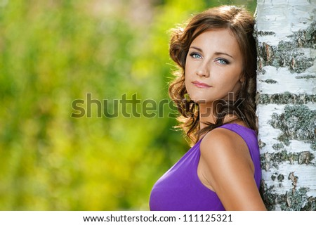 Beautiful young woman in purple dress is based on sad birch, against green of summer park.
