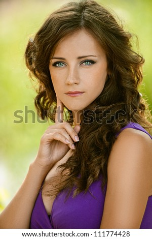 Beautiful young woman in purple dress thought, against green of summer park.