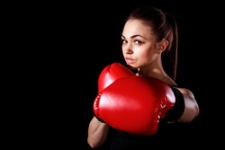 Beautiful young woman in red boxing gloves over black background