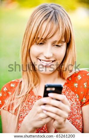 Beautiful young woman in red dress dials number on mobile phone, against summer city park.