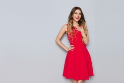 Beautiful young woman in red dress is holding hand on chest, looking at camera and smiling. Three quarter length studio shot on gray background.