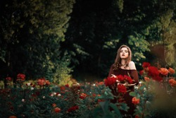 Beautiful young woman in red dress with long curly hair posing near roses in a garden. The concept of perfume advertising.