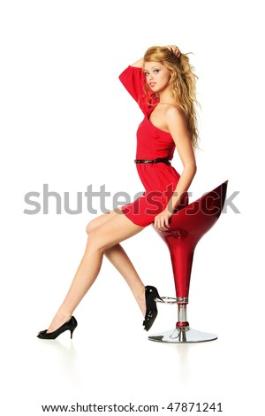 Beautiful young woman in red sitting on bar chair, isolated over white background.