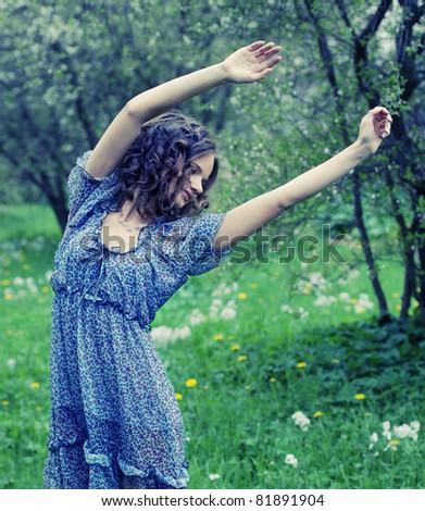 Beautiful young woman in romantic dress relaxing in garden