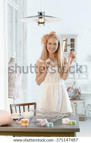 Beautiful young woman in romantic retro style, smiling, making home decoration.