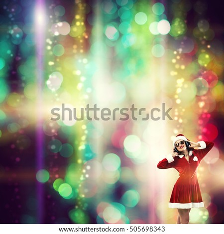 Beautiful young woman in Santa Claus clothes and headphones over bokeh background #505698343
