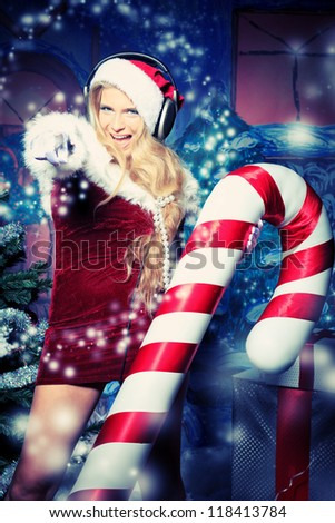 Beautiful young woman in Santa Claus clothes and headphones over Christmas background.