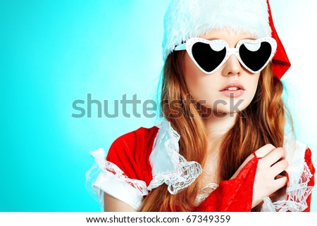 Beautiful young woman in Santa Claus clothes over blue background.