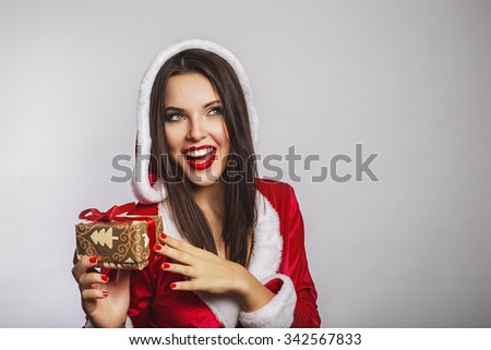 e372a981b6fe Beautiful young woman in Santa Claus clothes over Christmas background.  Smiling woman holding cristmas gift