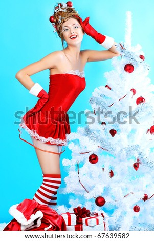 Beautiful young woman in Santa Claus clothes posing over Christmas background.