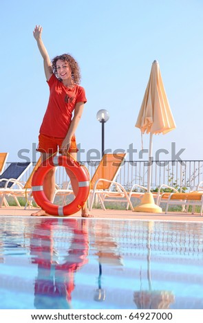 Beautiful young woman in shorts and T-shirt keeps red life buoy - stock photo