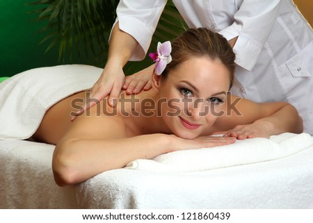beautiful young woman in spa salon getting massage, on green background
