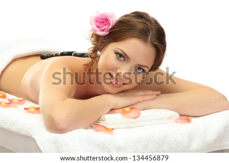 beautiful young woman in spa salon with spa stones, isolated on white