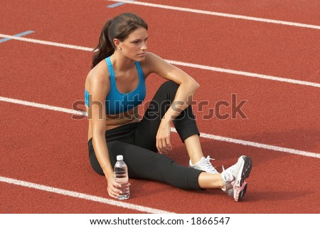 Beautiful Young Woman in Sports Bra with Water Bottle on Track Relaxing