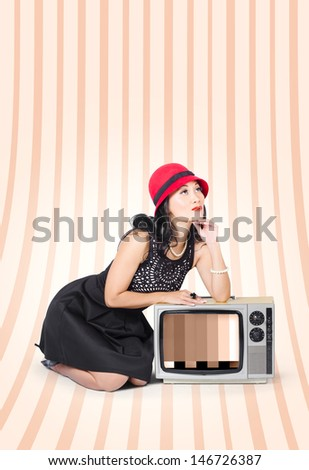 Beautiful young woman in studio thinking on old fashion tv in classic clothes signifying retro pinup style