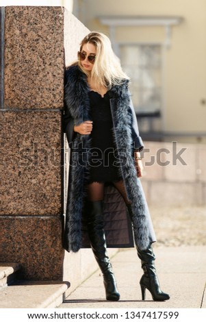 Beautiful young woman in sun glasses and fur coat posing with luxury bags and accesories while standing walking outdoors. Female fashion city lifestyle outfit spring or autumn shopping concept #1347417599