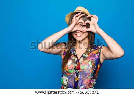 Beautiful young woman in sun hat is showing heart shape hand sign. #756819871