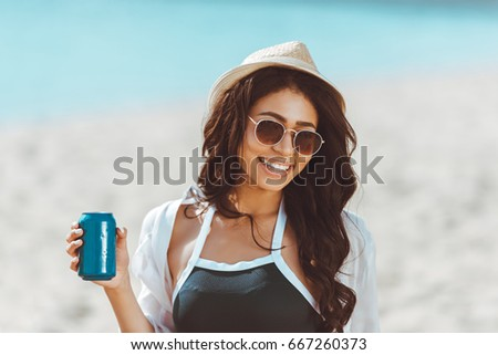 Beautiful young woman in sunglasses and straw hat holding soda can and smiling at camera  #667260373