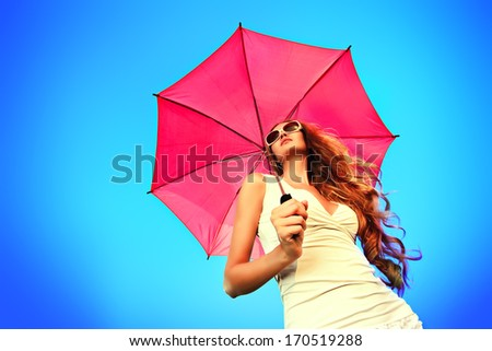 Beautiful young woman in sunglasses holding umbrella over sky.