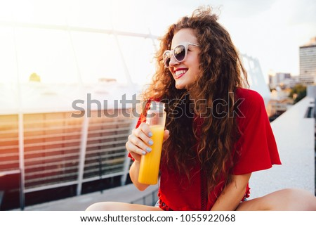 Beautiful young woman in sunglasses holds a bottle with fresh juice, looking away, sitting on marble slab in a sunny day, outdoors. Stock foto ©