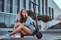 Beautiful young woman in sunglasses is sitting on her electro scooter near big glass building.