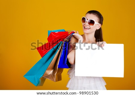 Beautiful young woman in sunglasses with shopping bags isolated on yellow background - stock photo