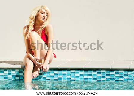 beautiful young woman in swimsuit by the swimming pool