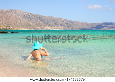 Beautiful young woman in swimsuit with sunhat, relaxing on the sunny beach. Chill out concept