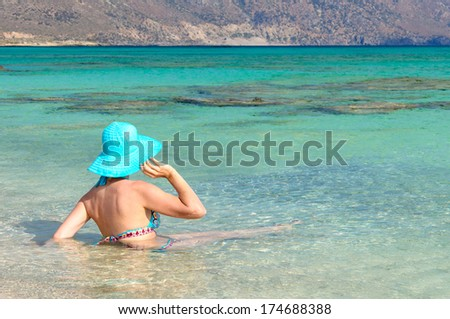 Beautiful young woman in swimsuit with sunhat, relaxing on the sunny beach. Chill out concept - stock photo
