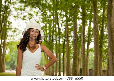 Beautiful young woman in the Parisian countryside along a tall row of trees.
