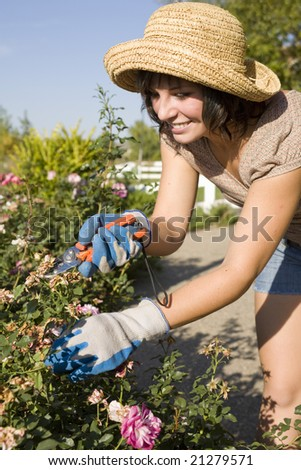 Beautiful young woman in the yard gardening