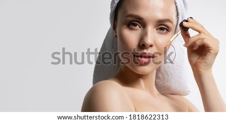 Beautiful young woman in towel apply moisturizing facial serum isolated on white background. Morning daily beauty luxury procedures. Skincare and rejuvenation concept