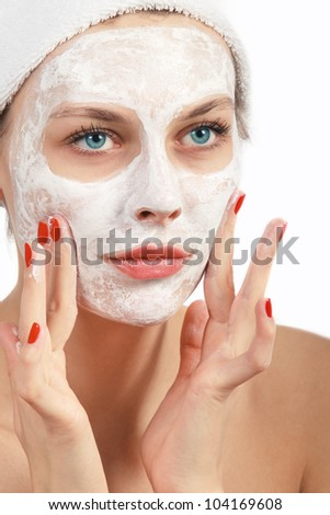 Beautiful young woman in towel doing cosmetic mask on her face
