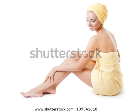 Beautiful young woman in towel sitting on the floor and stroking her beauty legs