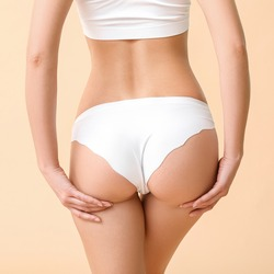 Beautiful young woman in underwear on color background. Concept of cellulite