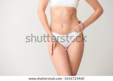 Beautiful young woman in underwear on light background. Concept of plastic surgery Stock fotó ©