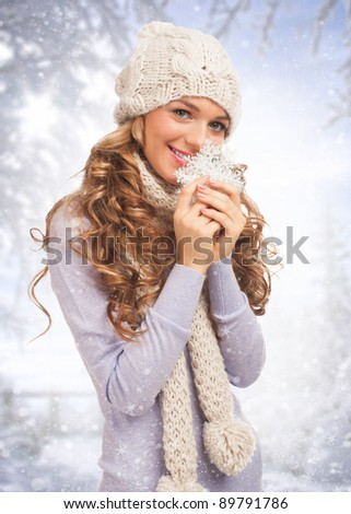 Beautiful young woman in warm clothing holding big snowflake in her hands, against winter forest