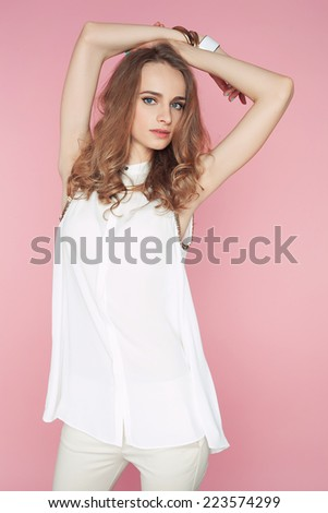 Beautiful young woman in white clothes posing on pink background