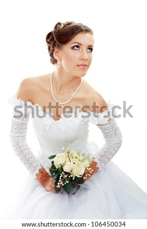 Beautiful young woman in white dress and pearl necklace beige background with henna tatoo applyed to her hands and with wedding bouquet