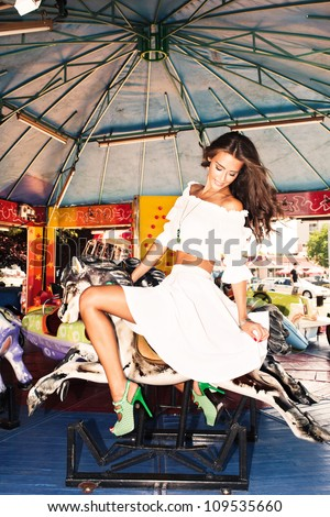 beautiful young woman in white dress outdoor in amusement park summer day