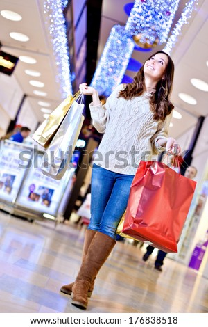 Beautiful young woman in white knitted sweater and blue jeans posing with shopping bags in mall during the Christmas sale.