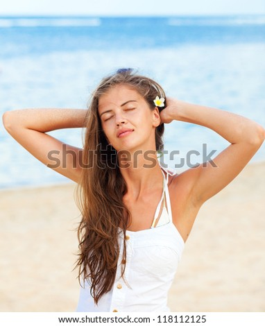 beautiful young woman in white with frangipany flower enjoying on beach