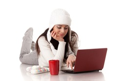 Beautiful young  woman in winter clothes with laptop lies on a white background.