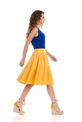Beautiful young woman in yellow skirt, blue top and wedge shoes is walking and looking away. Side view. Full length studio shot isolated on white.