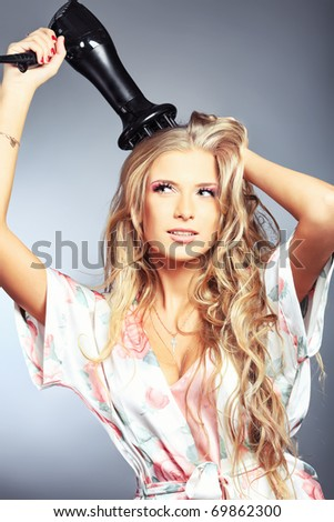 Beautiful young woman is blowing dry her hair. Studio shot over grey background.