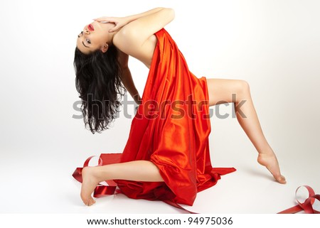 Beautiful young woman is covered with red cloth. - stock photo