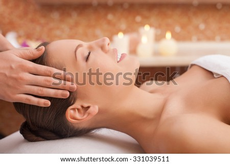 Beautiful young woman is getting head massage at spa. She is lying and smiling. Her eyes are closed with pleasure. The female hands of masseuse are massaging her carefully